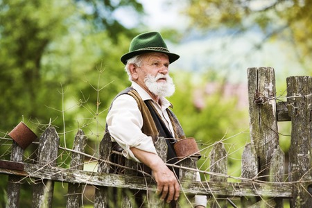 gaffer: Old farmer with beard and hat standing by the lath fence with empty tins on top