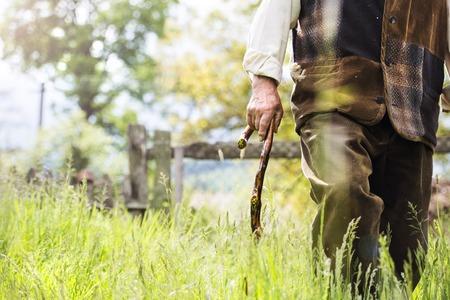 hombre con barba: Primer plano de viejo granjero con barba y sombrero est� caminando en su patio trasero