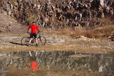 Cyclist man standing with his bike is reflecting in water puddle photo