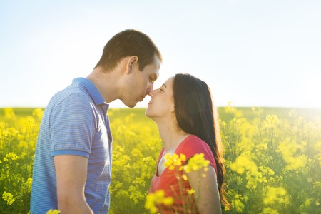 Happy young couple in love kissing in yellow colza field photo
