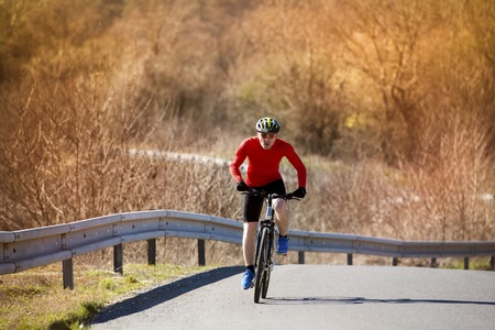 Cyclist man riding mountain bike on asphalt road photo