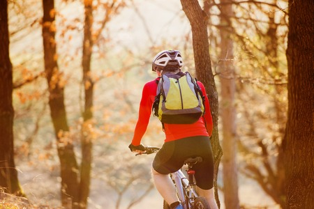 Cyclist man riding mountain bike on outdoor trail in autumn forest photo