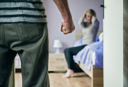 Mature woman sitting on the bed is scared of a man  Woman is victim of domestic violence and abuse  Stock Photo