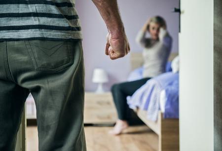 violencia intrafamiliar: Mujer madura se sienta en la cama tiene miedo de un hombre la mujer es v�ctima de la violencia dom�stica y el abuso Foto de archivo