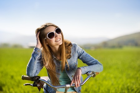 Pretty young girl with bike in green field photo
