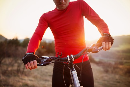 Detail of cyclist man riding mountain bike on outdoor trail in sunny meadow photo