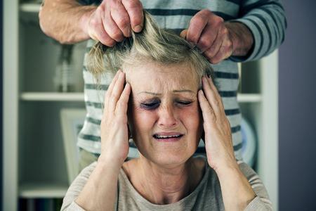 Portrait of woman victim of domestic violence  Man abusing senior woman with black eye- photo