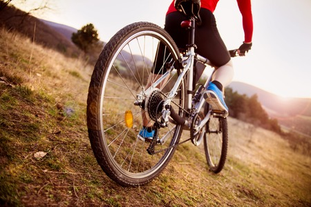 Detail of cyclist man feet riding mountain bike on outdoor trail in sunny meadow