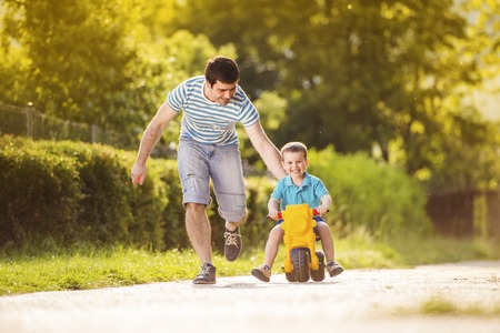 Young father with his little son on motorbike in green sunny park photo