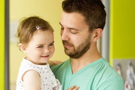 two year: Indoor portrait of young father hugging his little daughter