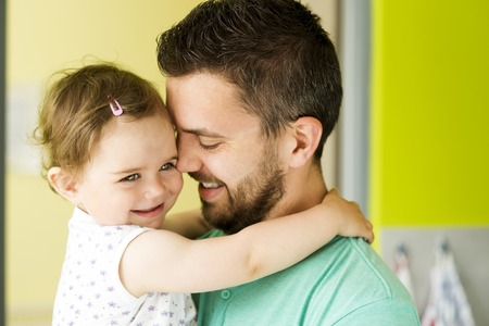indoors: Indoor portrait of young father hugging his little daughter