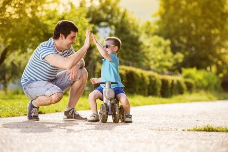 Mladý otec se svým malým synem na motorce v zeleném slunné parku