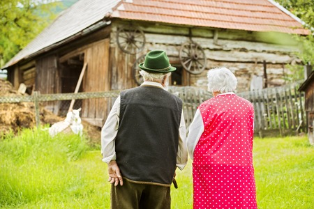adult 80s: Rear view of old farmers couple standing by their farmhouse