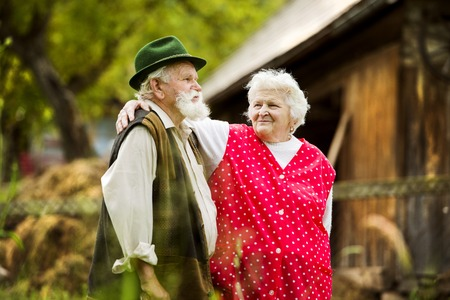 Outdoor portrait of old farmers couple standing by their farmhouse photo