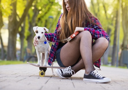 urban youth: Girl on skateboard with a dog