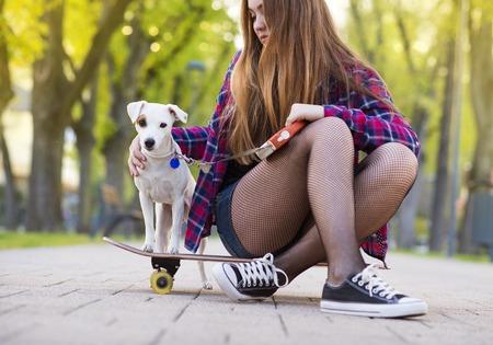 Girl on skateboard with a dog
