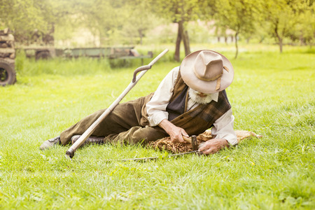 guadaña: Senior agricultor con guadaña para cortar el césped tradicionalmente