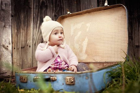 Happy little girl in warm clothes is sitting in retro suitcase in front of the fence in autumn nature photo