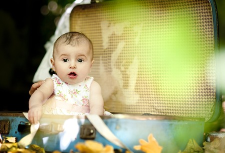 Cute baby girl sitting in old retro suitcase in summer nature photo