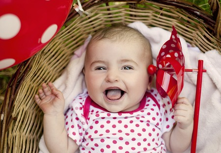 babies laughing: Cute baby girl lying down in basket in summer nature