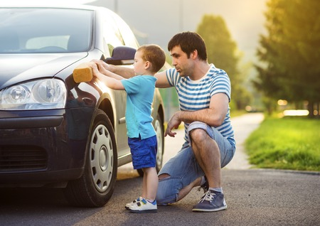 family activities: Young father with his little son washing car