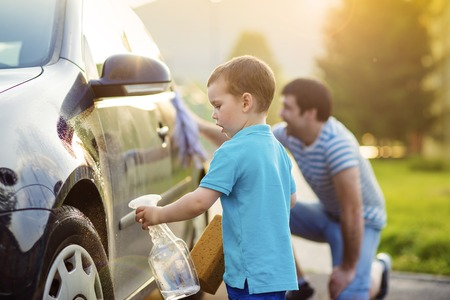 wash car: Young father with his little son washing car