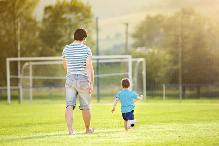 football pitch: Young father with his little son playing football on football pitch Stock Photo