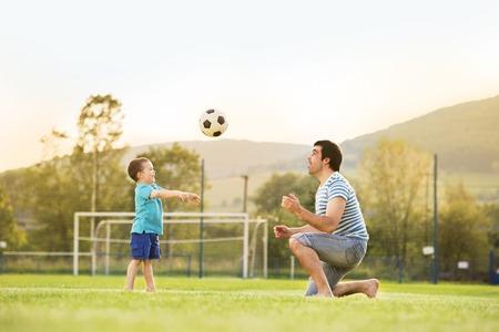 jugando futbol: Joven padre con su pequeño hijo jugando al fútbol en el campo de fútbol