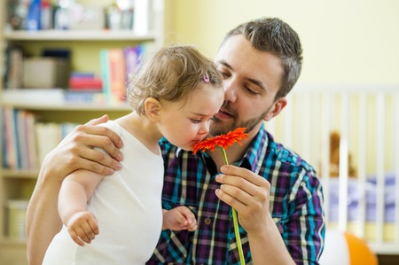 Portrait of a happy father with flower and his little daughter photo