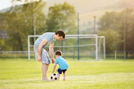Jonge vader met zijn zoontje voetballen op voetbalveld Stockfoto