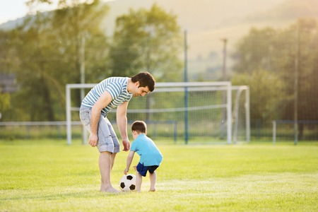 Young father with his little son playing football on football pitch Stock Photo
