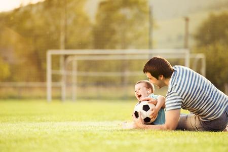 그의 작은 아들이 축구 경기장에서 축구를하는 젊은 아버지