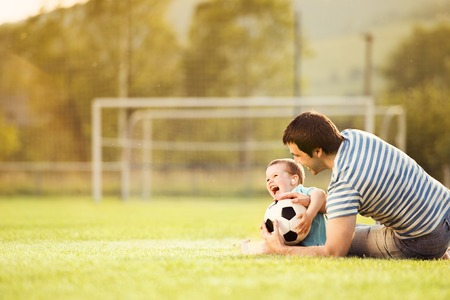 father with children: Young father with his little son playing football on football pitch Stock Photo
