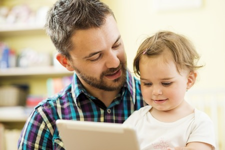 Portrait of a happy father and his little daughter using digital tablet at home photo