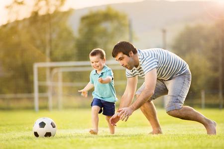 jugar: Joven padre con su pequeño hijo jugando al fútbol en el campo de fútbol