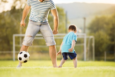 playing football: Joven padre con su peque�o hijo jugando al f�tbol en el campo de f�tbol