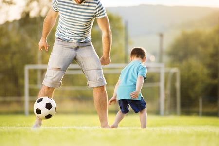 Joven padre con su peque�o hijo jugando al f�tbol en el campo de f�tbol photo