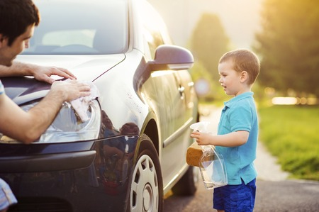 clean car: Young father with his little son washing car