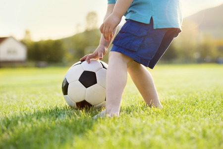 kids feet: Close-up of little boy playing football on football pitch Stock Photo