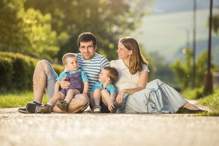 Happy family is relaxing and sitting on countryside road photo