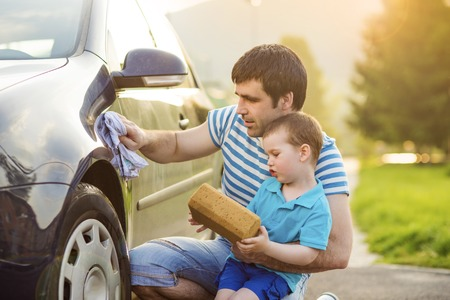 Young father with his little son washing car photo