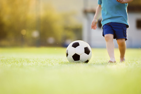 Close-up of little boy playing football on football pitch Stock Photo
