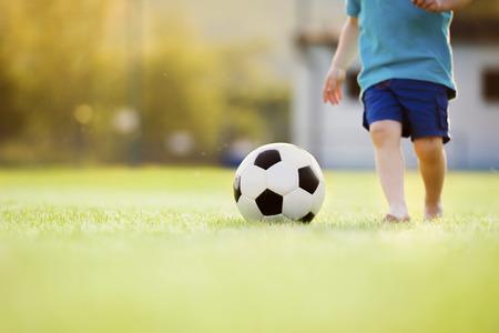 Close-up van de kleine jongen voetballen op een voetbalveld