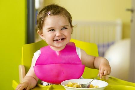 babero: Niña en silla está comiendo merienda en la cocina