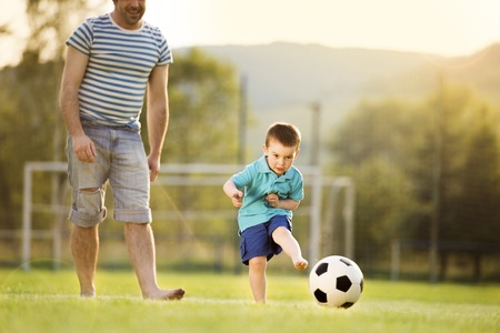 Young father with his little son playing football on football pitch photo