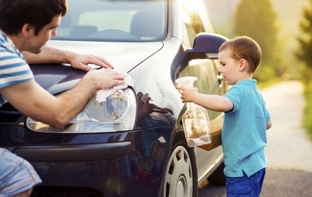 teaching adult: Young father with his little son washing car