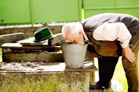 seau d eau: Vieux fermier se lave le visage avec de l'eau du seau