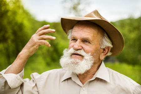 agriculturalist: Portrait of old farmer with beard and hat in his backyard Stock Photo