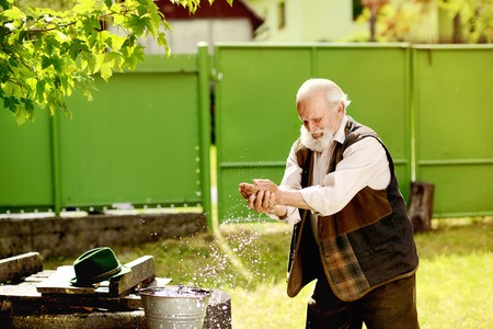 agriculturalist: Old farmer is washing his face with water from bucket