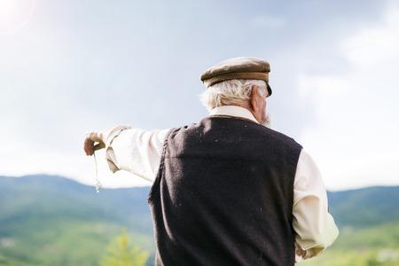 Old farmer with beard is walking in meadow photo